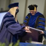 A woman in a graduation cap and gown receives an envelope from someone off camera. Behind her, a man at a lectern in a cap and gown smiles downward.