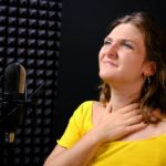A young woman holds her throat while standing near a microphone.