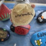 "Painted rocks featuring messages such as ""bee happy"" and ""hope"" sit on a table. Other rocks are painted to resemble a penguin, a lady bug and a strawberry. A tan rock that reads ""#PSHSpreadTheJoy"" sits in the palm of a hand shown above the other rocks."