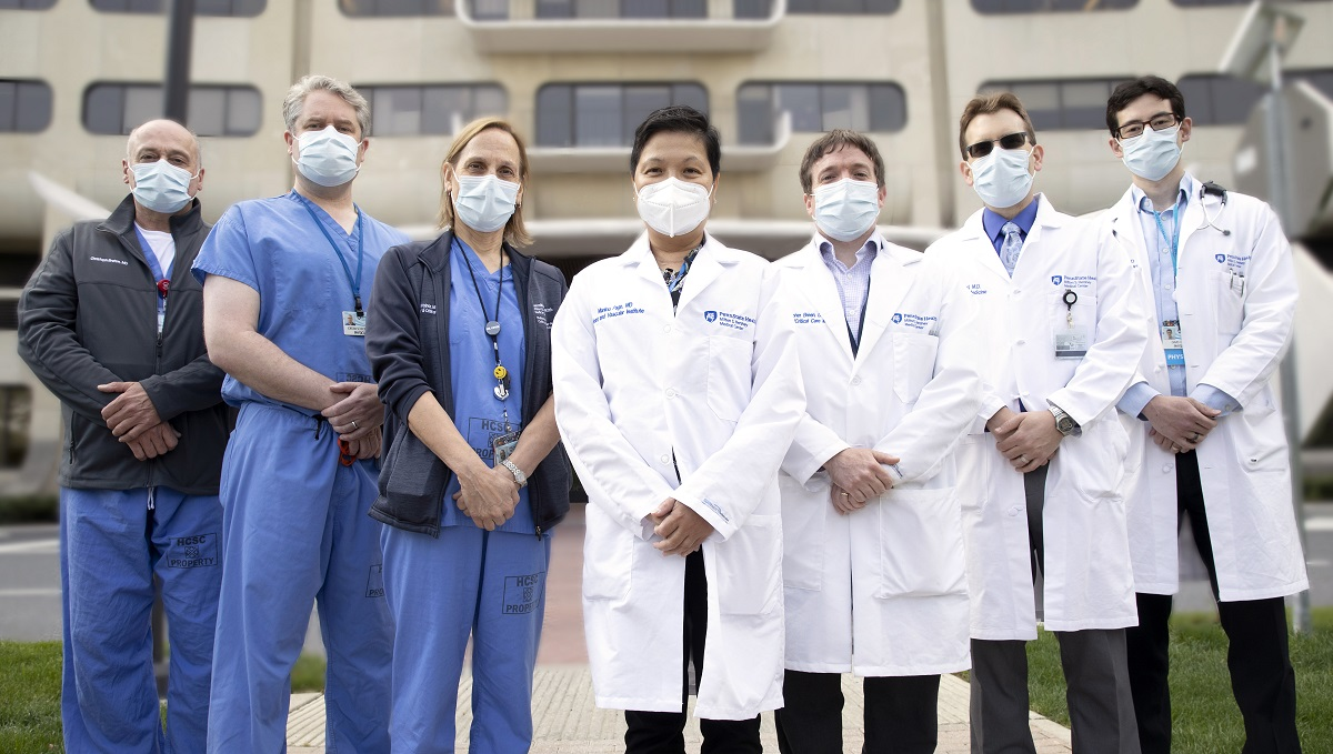 Seven physicians stand shoulder-to-shoulder, arms folded in front of them, outside Hershey Medical Center.