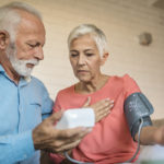 A woman has a blood pressure cuff on her left arm. A man standing next to her holds the monitor for it.