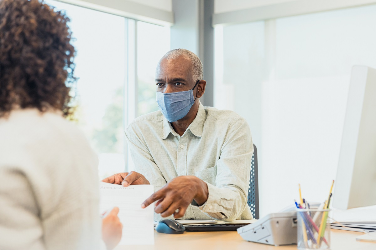 A man in a surgical mask sits in an office and points at a form held by a woman facing him across a desk.