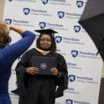A photographer takes a professional portrait of Nicole Waweru, a graduate of the Master of Public Health Program at Penn State College of Medicine, during the 51st commencement.