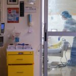 A doctor stands at the foot of a patient bed in a COVID-19 unit