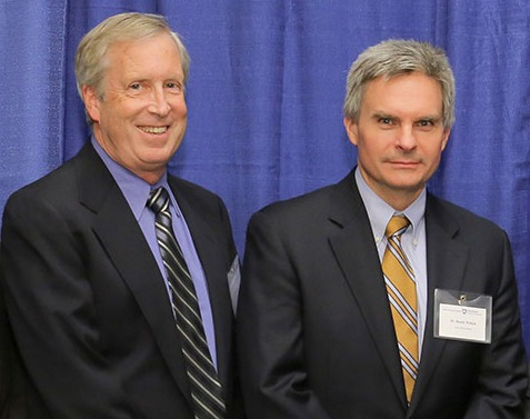 Barry Fell and Randy Haluck are seen wearing suits and standing in front of a professional photo background