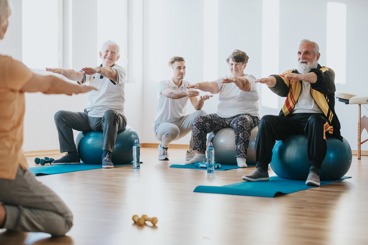 A group of seniors exercise on balls together in a gym.