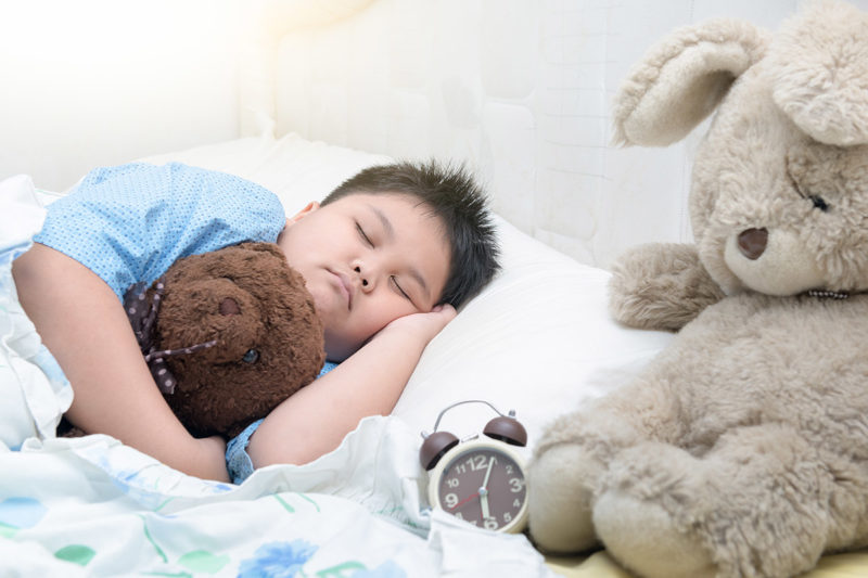 A child sleeps holding a small teddy bear while lying beside a larger stuffed animal.