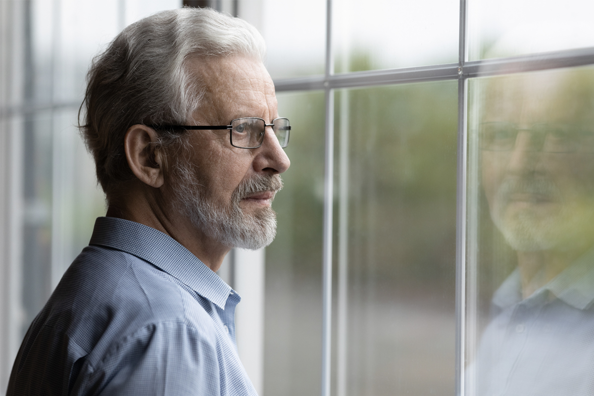 An older man wearing glasses looks out of a window.