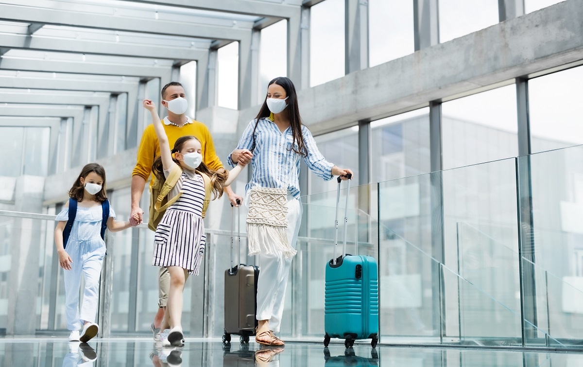 Family walking through airport with their luggage.
