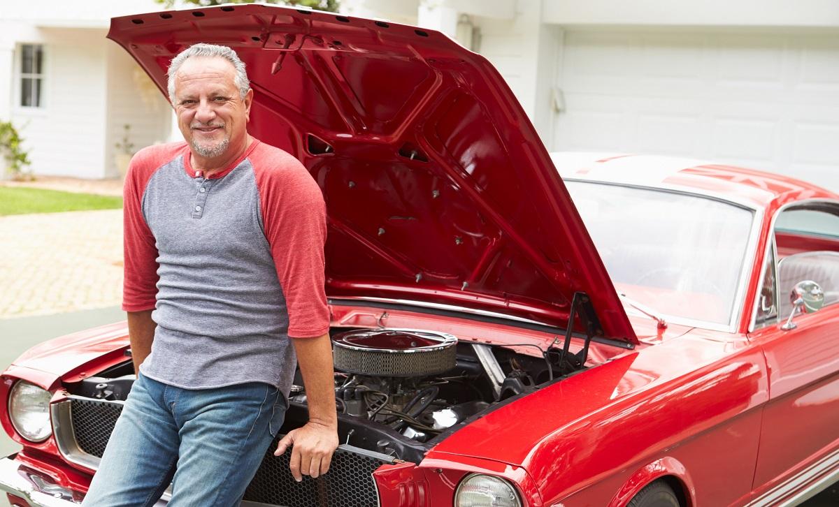 Retired senior man sitting on front of restored classic car.