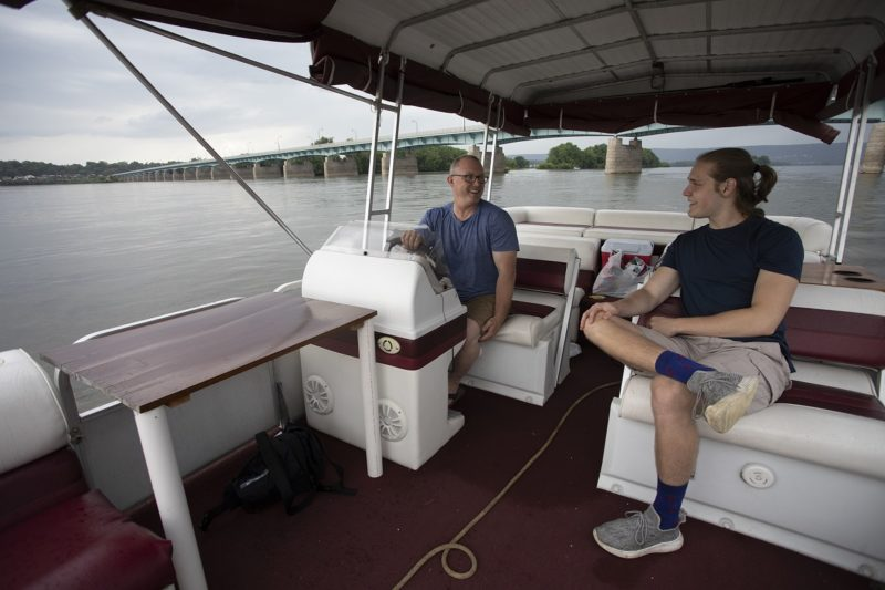 George Yatsky, who has short hair and wears glasses, shorts and a T-shirt, sits at the wheel of a pontoon boat and looks over at his son, who has a pony tail and wears a T-shirt, shorts and sneakers. A bridge stretched over a river in the background.