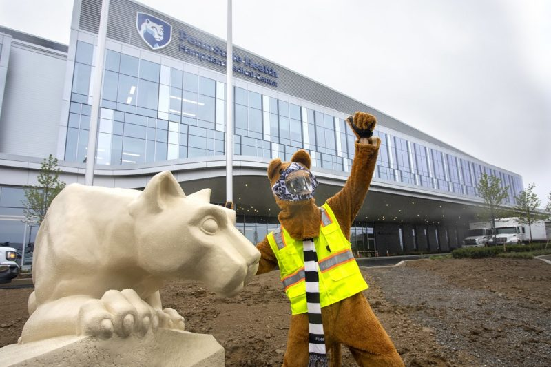 The Nittany Lion mascot raises its left arm as it touches the Nittany Lion statue with its left arm. The mascot is wearing a face mask, safety vest and scarf. Behind them is the newly constructed Penn State Health Hampden Medical Center, which has three stories and a sign that reads Penn State Health Hampden Medical Center. The top two stories are all glass windows.