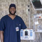 Nurse Viniquinn Terry, who has a beard and wears scrubs, smiles as he stands with medical equipment used in the cardiovascular intensive care unit.