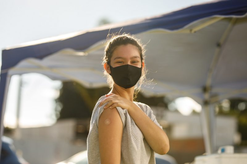 A girl in a mask shows the bandage where she received the vaccine on her arm.