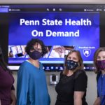 Four women wearing facemasks stand in front of a screen that reads Penn State Health OnDemand.