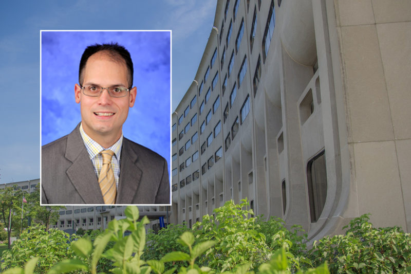 A head and shoulders professional portrait of William Calo against a background image of Penn State College of Medicine.
