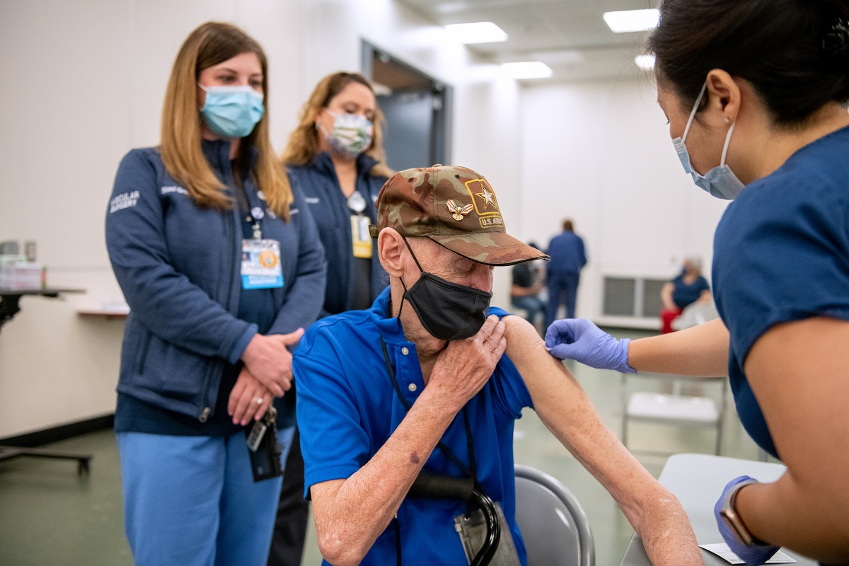 Robert Trate, wearing a mask and ball cap, rolls up his sleeve to receive a vaccination as registered nurse Judy Dee, wearing scrubs and a mask, leans toward him and cleans his bare upper arm. Physician Assistant Staci Gross Surgical Scheduler Jackelyn Ortega, wearing scrubs and masks, stand in the background.