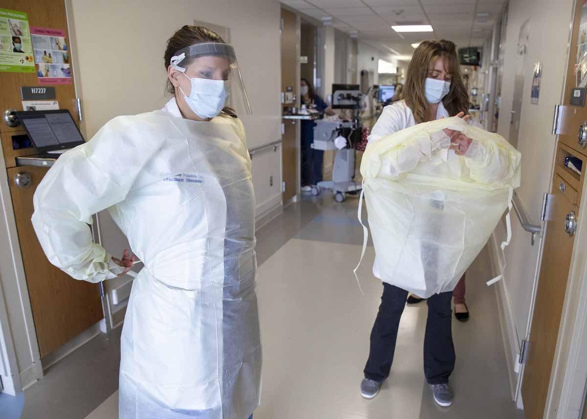 Dos mujeres se ponen equipo de protección personal en el pasillo de un hospital.