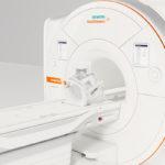 An MRI machine sits in a plain-looking room.