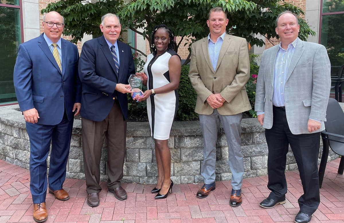 Four men and one woman stand in a courtyard and smile at the camera. From left are Steve Massini, Penn State Health CEO; Jim George, Penn State Health director of community relations; Michelle Phillips, United Way of the Capital Region (UWCR) campaign manager; Anthony Worrall, Reynolds Restoration Services president and UWCR campaign vice chair; and Tim Fatzinger, UWCR president and CEO, celebrate the Outstanding Campaign Team Award. Jim George and Michelle Phillips are holding a Plexiglas trophy engraved with a United Way award won by Penn State Health and Penn State College of Medicine.