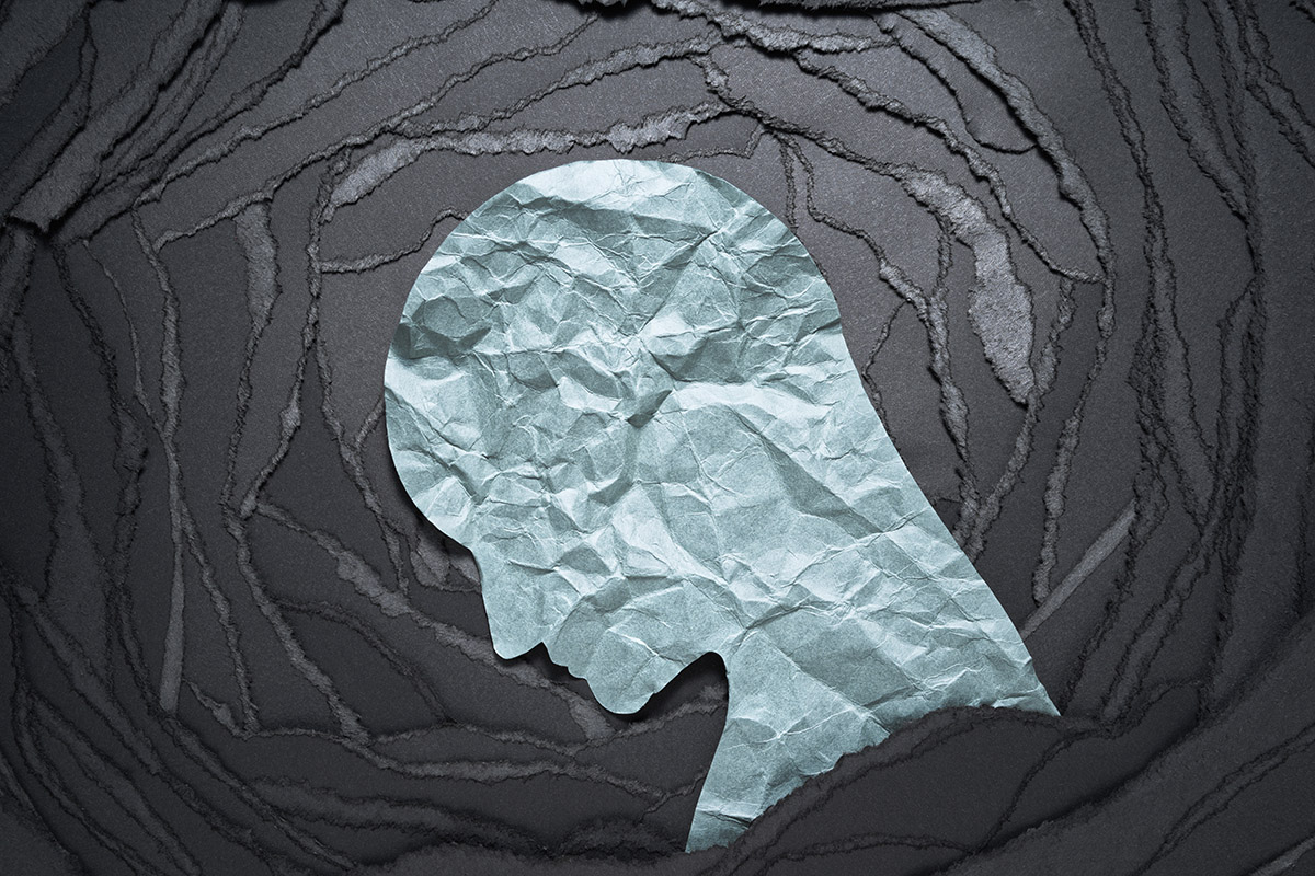 A silhouette of a person's head looking down.