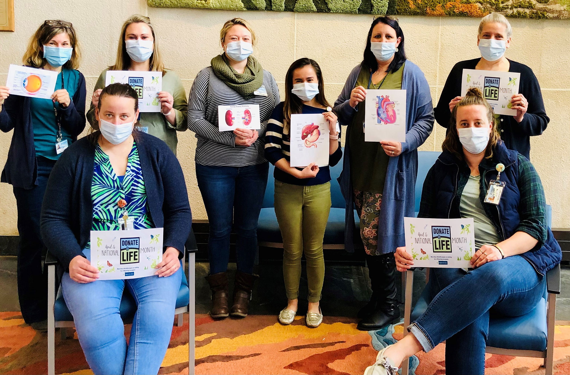 A group of eight people, six standing and two sitting, are pictured wearing face masks and holding signs.