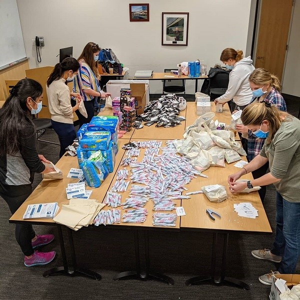 Six people wearing facer masks are standing around the edges of a large table, which has women's hygiene products spread out on it.
