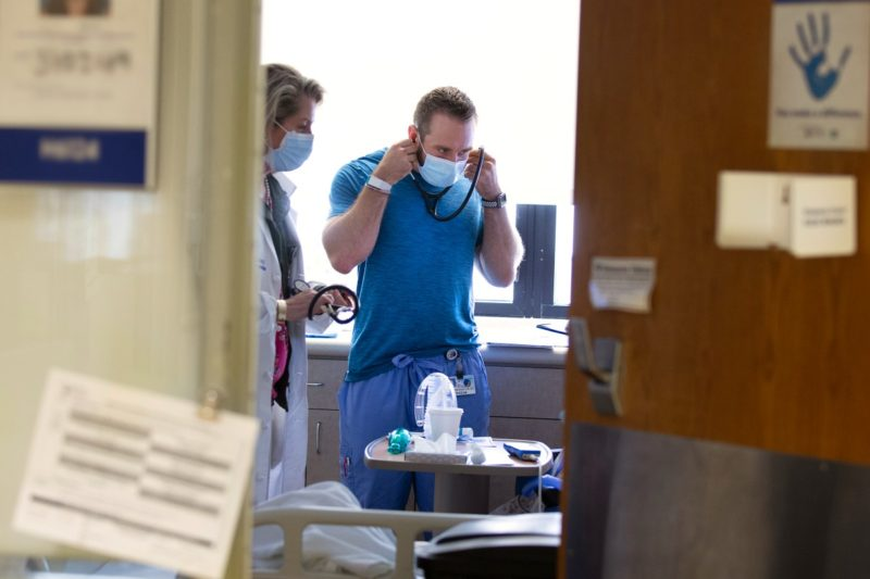 Two doctors stand in a patient room at Penn State Health Milton S. Hershey Medical Center.