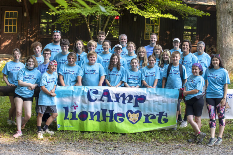"""A group of teens and a few adults pose behind a large sign that reads """"Camp Lionheart."""" A building and some trees are in the background."""