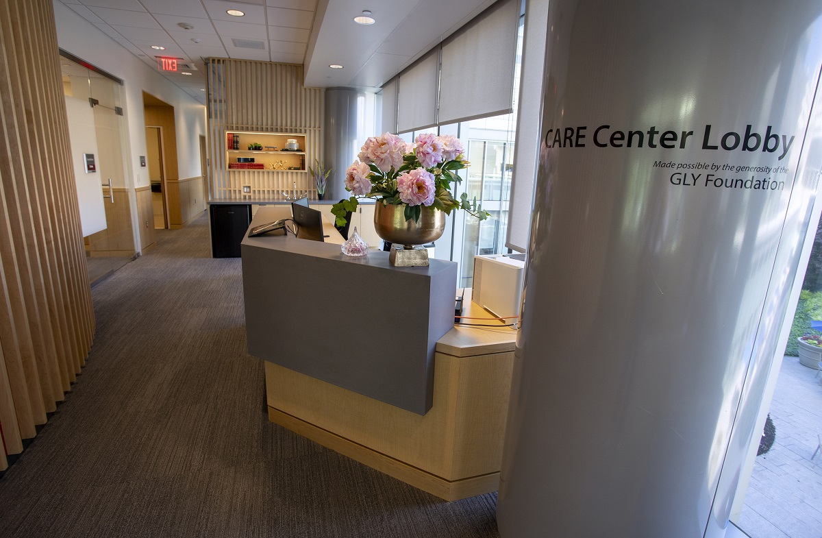 """The lobby of the Cancer Assistance and Resource Education Center in Penn State Cancer Institute shows a reception desk with a bowl of flowers on it, a column on the right with the words """"CARE Center Lobby"""" on it and a wall with slats on the left."""