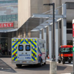 An ambulance sits outside the front entrance of an emergency department