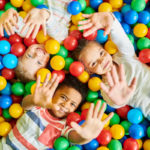 Three young children lie on their backs in a pit of colorful balls, their hands extended upward toward the camera.