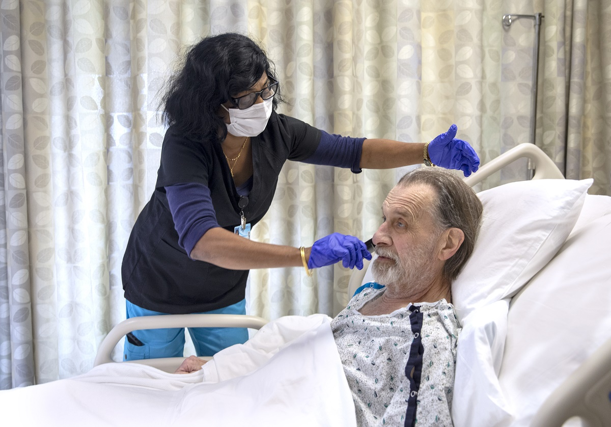 Sherly George, a nursing assistant at Penn State Health Holy Spirit Medical Center, combs the hair of patient Clay Landry Jr. She is leaning over him as he sits propped up in a hospital bed. She is wearing a long-sleeved top, glasses, face mask and surgical gloves. He is wearing a hospital gown and has a beard.