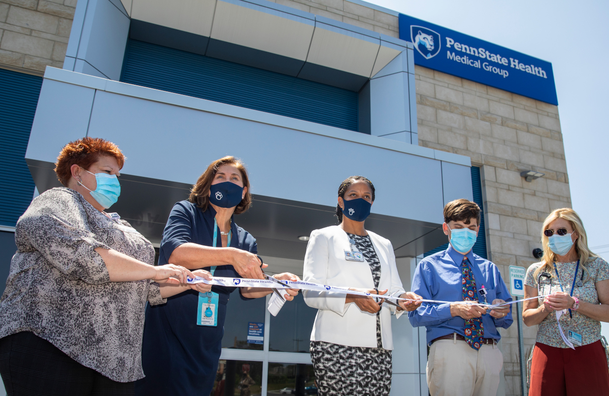 A group of officials cut a ribbon outside of a new medical practice