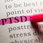 """Close-up of the acronym """"PTSD"""" in a book being highlighted by a marker."""