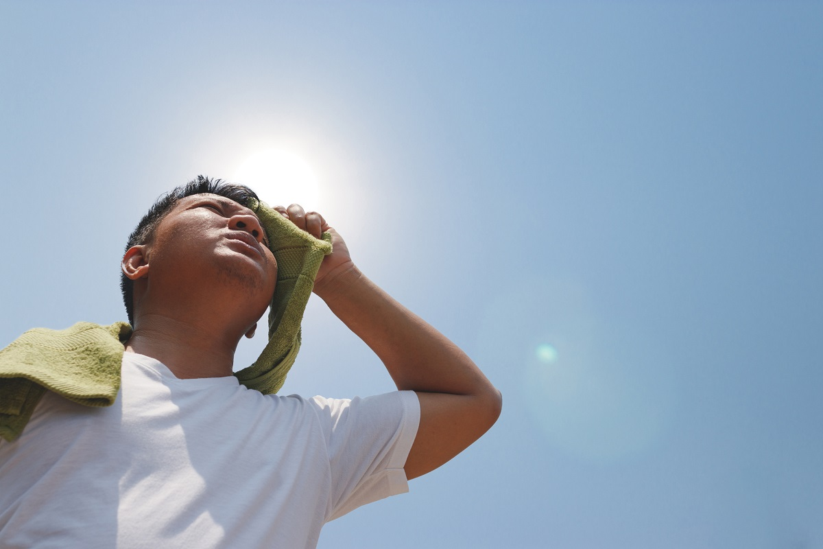A man holds a towel to his forehead as the sun blazes overhead.