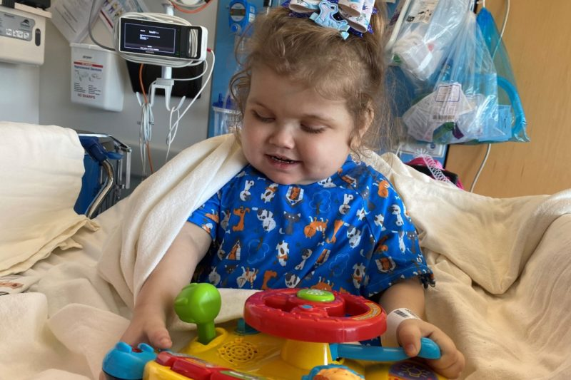 A young girl with a bow in her hair sits in a hospital bed with medical equipment behind her. She is playing with a plastic toy.