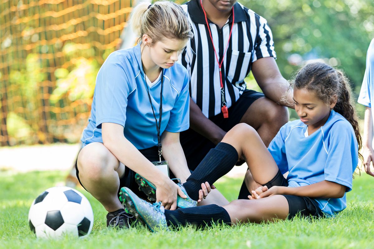A young girl sits on the ground with her knee in the air, in obvious pain. Two adults tend to her. A soccer ball is nearby.