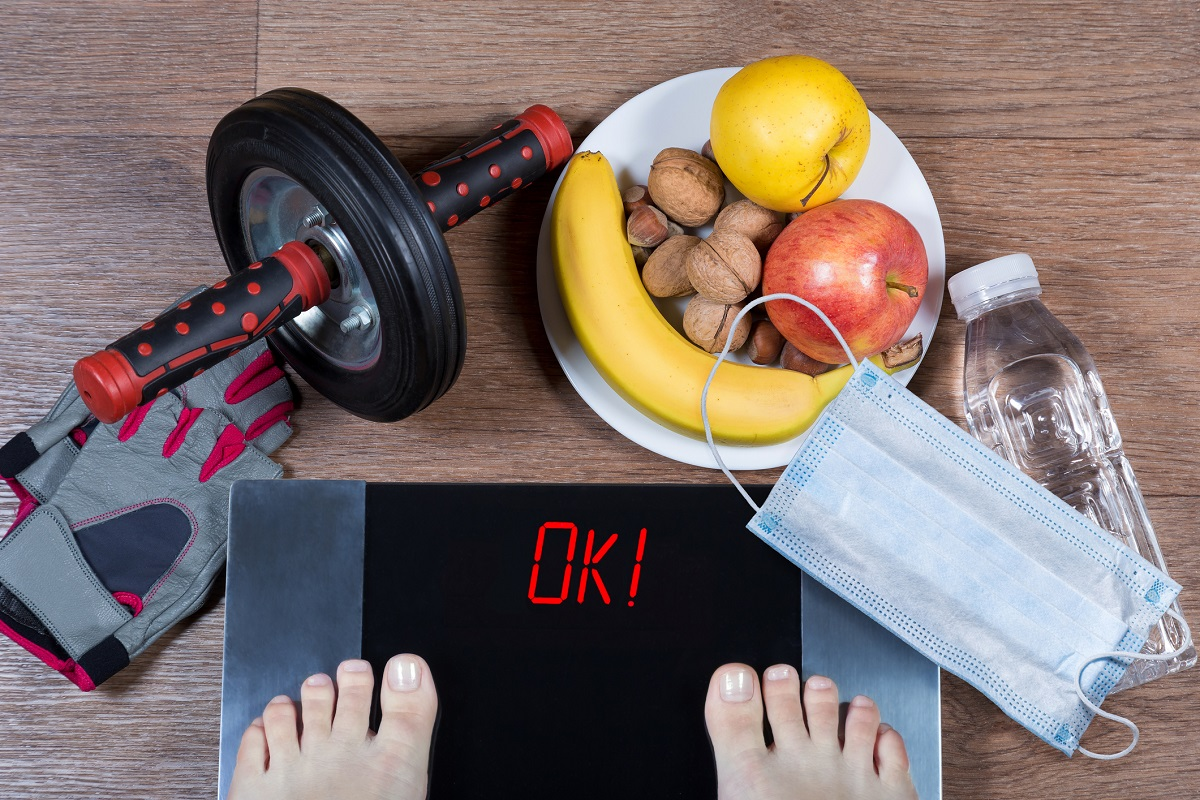 Person checks weight after quarantine. Digital scales with word ok surrounded by sport accessories, healthy food, water bottle and face mask.