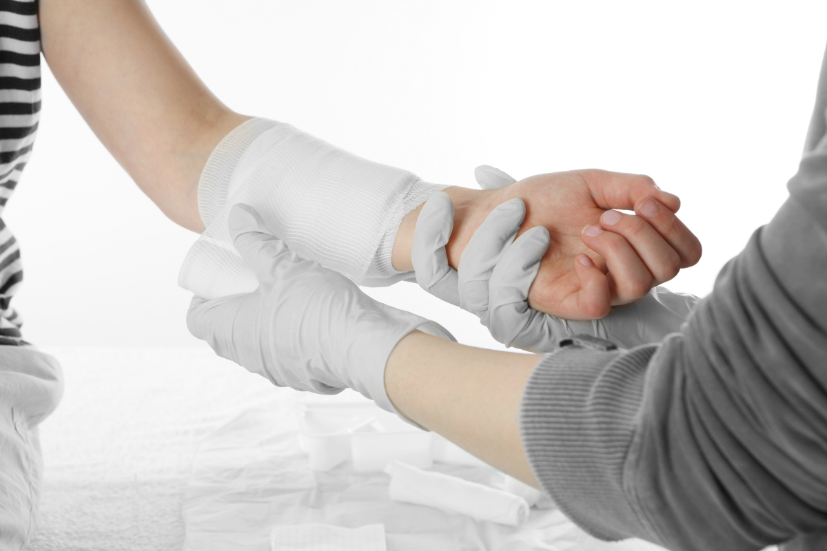A close up of a provider dressing a wound on a patient's arm