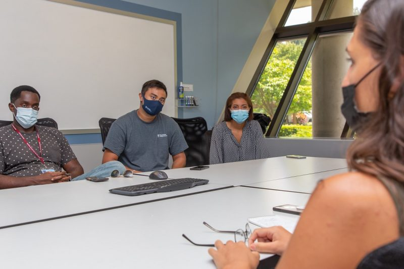 Three people in masks sit at a table speak to another woman in a mask.