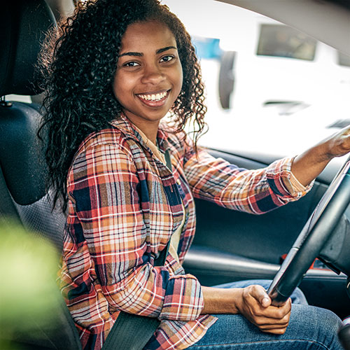 Young teen driver behind the steering wheel of a motor vehicle.