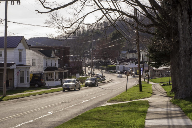 Houses line a street on which a couple of cars are parked. Some trees and telephone poles are also in the shot.