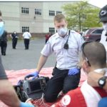 Four men are circled around a piece of equipment in a parking lot. They wear surgical masks. Two wear uniforms. Behind them other men and women in uniform stand in the parking lot.