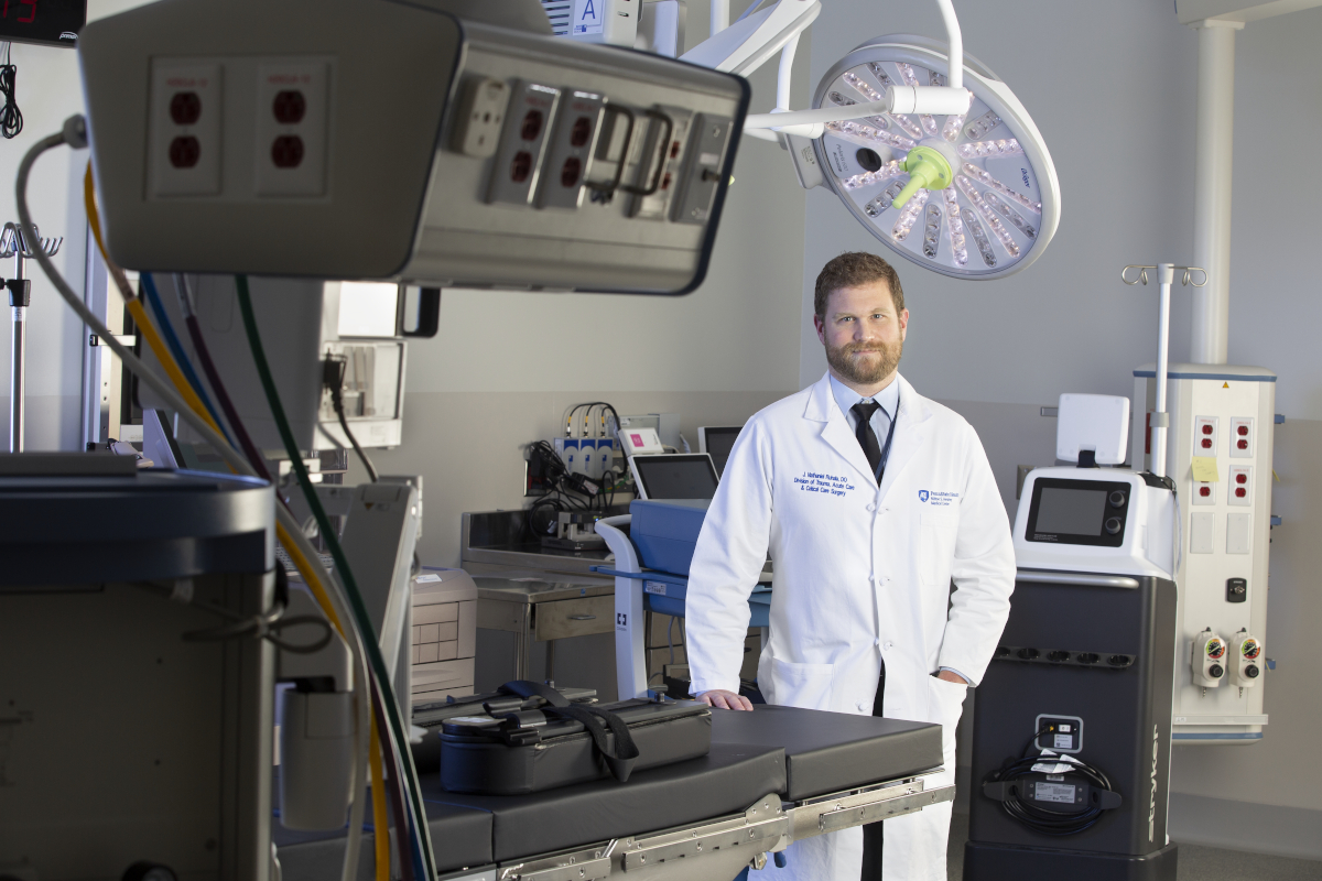 Dr. J. Nathaniel Ruhala, wearing a white medical coat, poses for a photo while standing in a hospital operating room. An overhead light and various surgical equipment is placed throughout the room.
