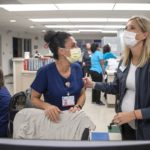 Two women in surgical masks and scrubs laugh at nurse's station in a hospital hallway. Behind them, other health care workers cluster.