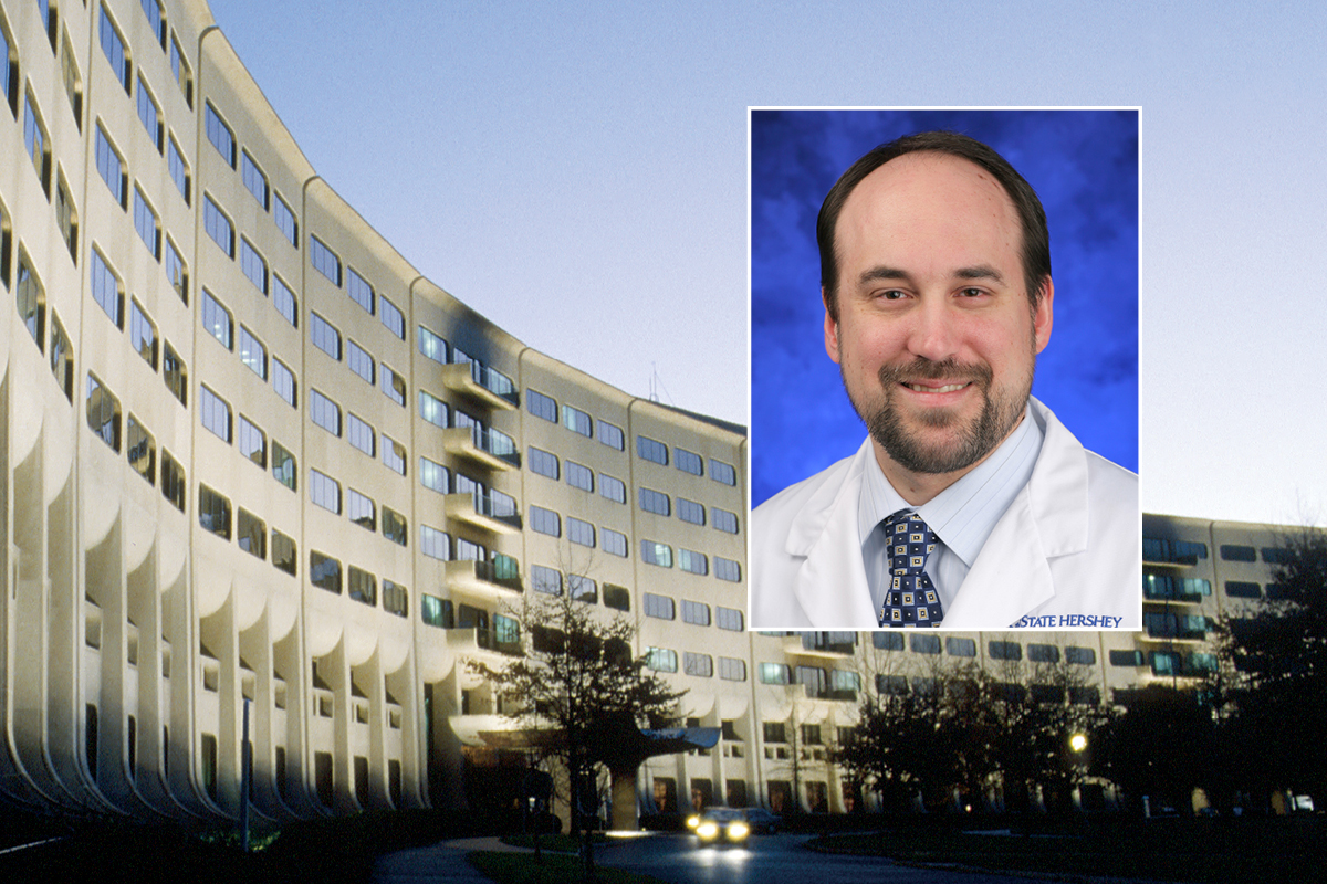 A head and shoulders professional portrait of Gregory Lewis against a background photo of Penn State College of Medicine