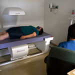 A woman participating in a clinical trial lays on a table in an exam room while a healthcare provider runs a test