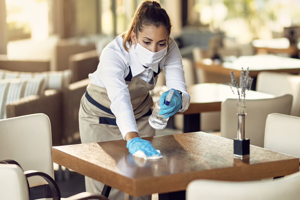A worker in a cafeteria sprays and wipes down a small table. She is wearing a mask.