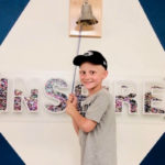 """A boy wearing a baseball cap faces the camera and smiles, standing in front of a bell that hangs on a wall along with the word """"INSPIRE"""""""